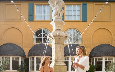 woman drinking wine by hotel courtyard fountain