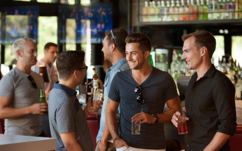 men talking at a bar with drinks in hand