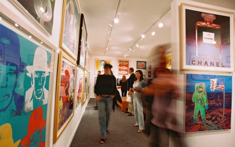 individuals walking through gallery of prints on wall