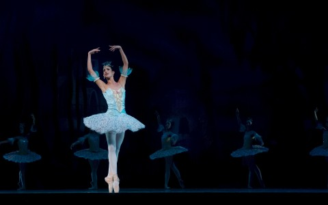 Ballerina on stage dancing in light blue tutu with line of ballerinas in background