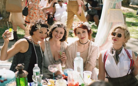 Four women having drink outdoors in Jazz Age attire