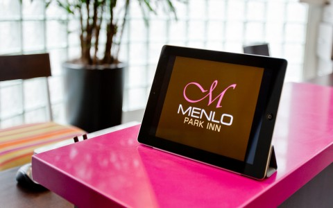 ipad on the check in desk with Menlo logo displayed.
