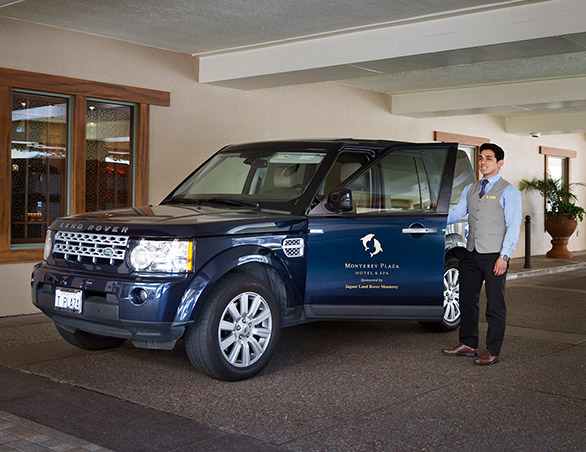 Staff member in uniform standing next to Land Rover with hotel logo