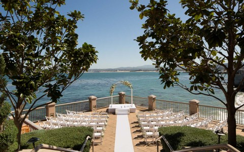wedding ceremony reception setup with chairs and alter with ocean view