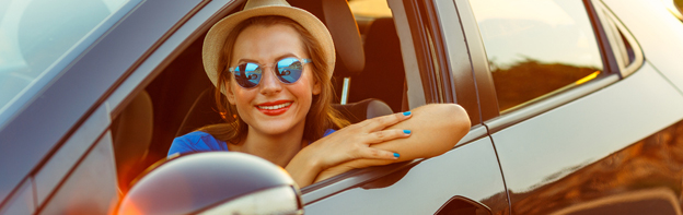 girl wearing sunglasses and fedora leaning out of car window smiling