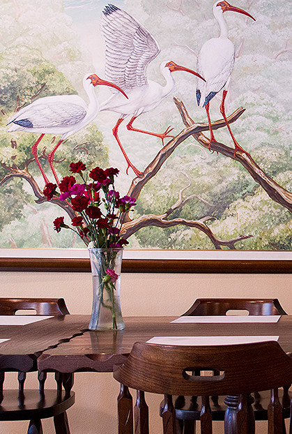 Painting of white birds on tree behind wooden table in dining area
