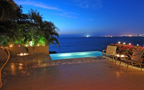 Nighttime shot of outdoor hot tub with lounger overlooking ocean