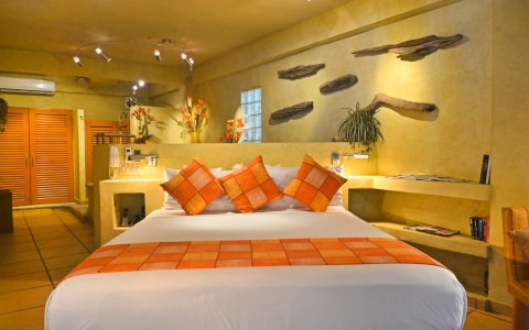 Room with king bed & bright orange pillows