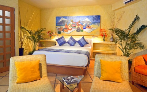 Room with king bed, nightstands, vibrant wall art & woven chairs