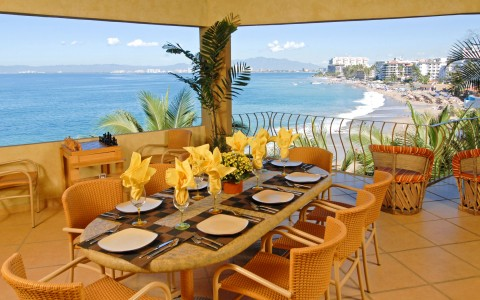 Dining table set for meal on villa balcony with ocean view
