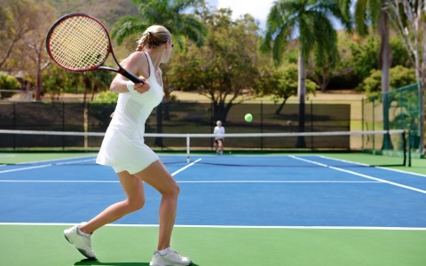 Woman ready to hit tennis ball with racket