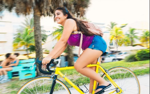 girl riding yellow bicycle