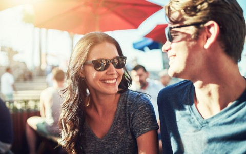 young couple with sunglasses on looking at each other