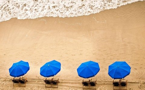 four blue beach umbrellas and chairs in the sand