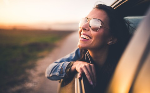 woman wearing aviators smiling with her head out the window of a car
