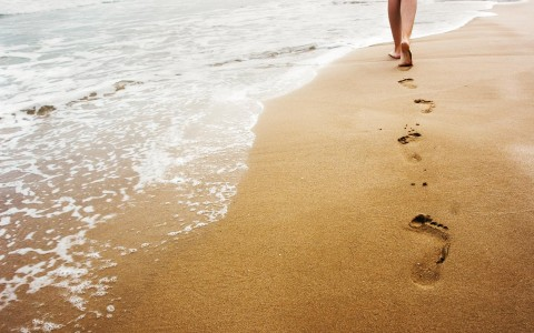 a woman walking on the beach leaving footprints behind