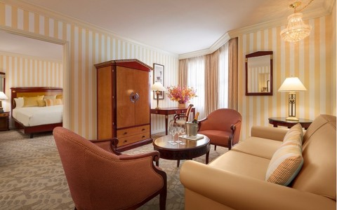 Grand Deluxe Suite with living area, two chairs, coffee table and sofa, bedroom in the back with king size bed