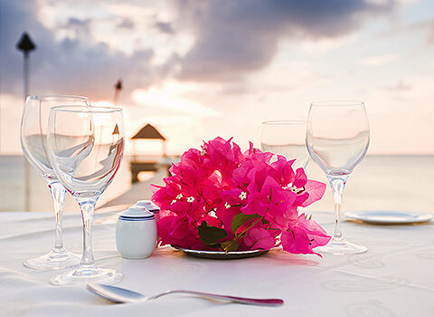 Table on the beach with white table cloth with wine glasses and flowers
