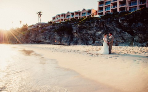 Bride and groom standing on beach holding hands for photo, with the sun glaring in the corner