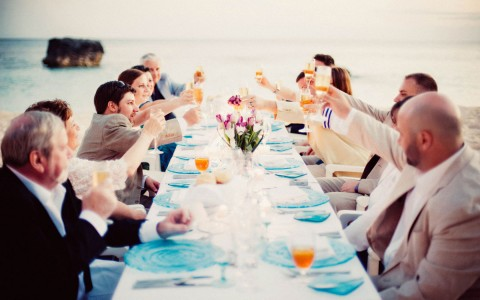 Elongated table seated with wedding party along the beach, they are raising their glasses