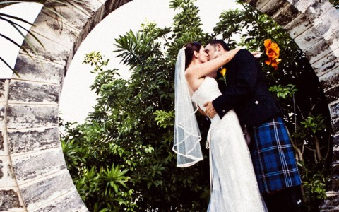 Bride and groom kissing under circular outdoor statue