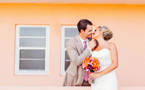 Bride and groom kissing and posing for photo in front of a pink wall with two windows