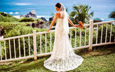 A bride in her wedding dress with orange bouquet, she is posing on white railing overlooking rocky beach cove