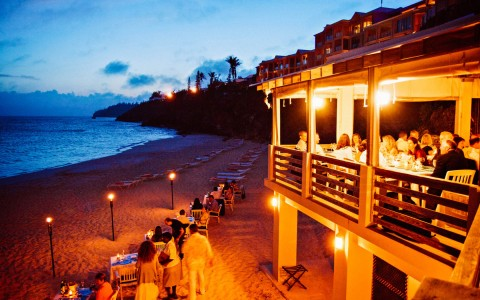 Wedding ceremony taking place at night on the beach property, some tables are set up on the sand below an outdoor dining deck