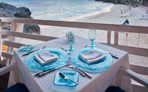 Table for two set with blue plates and dining wear overlooking beach on second level