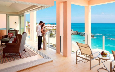 Man embracing woman from behind as they look over balcony of their living room that has an ocean view