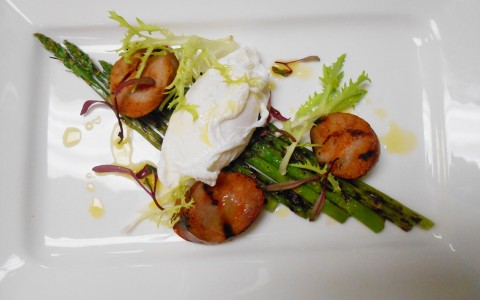 Burrata cheese appetizer on top of grilled asparagus on white plate