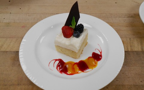 Piece of dessert custard cake with berry garnish on a white round plate with red and yellow decorative sauce