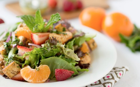 Field greens salad with sliced strawberries, mandarin oranges, and chunks of chicken served in a dish