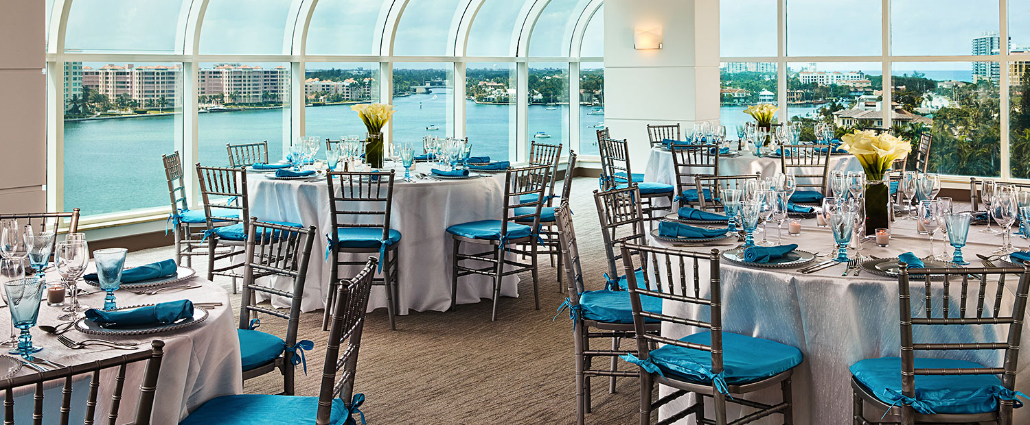 Tables set elegantly for event with aqua & white decor & waterfront view