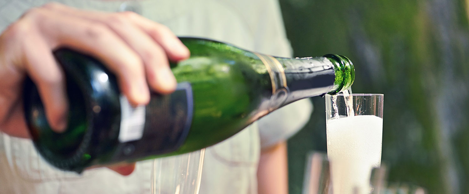 Close-up of person pouring champagne