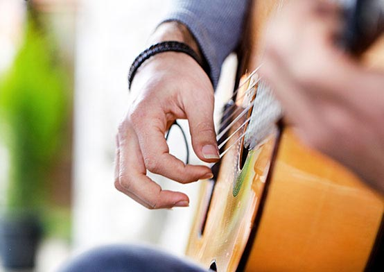Close up of hand playing acoustic guitar
