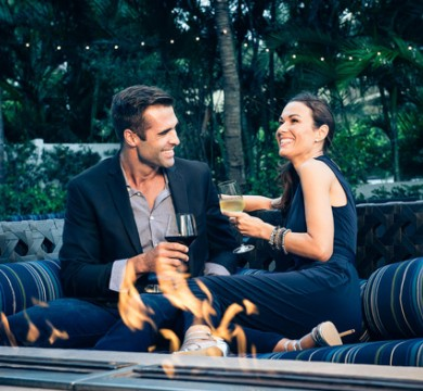 Couple lounging on couch by fire pit drinking wine