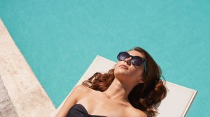 A woman lounges poolside