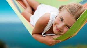 A young girl smiles in a hammock