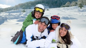 Family of four pose in ski gear on snowy slopes